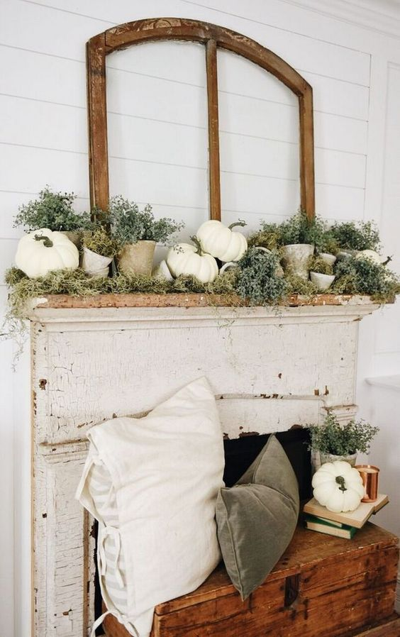a chic rustic fall mantel with faux pumpkins, moss, greenery in terra cotta pots and with matching velvet pillows in the fireplace
