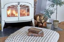 a chunky knit square ottoman is a cozy and warming piece to place in front of your mantel
