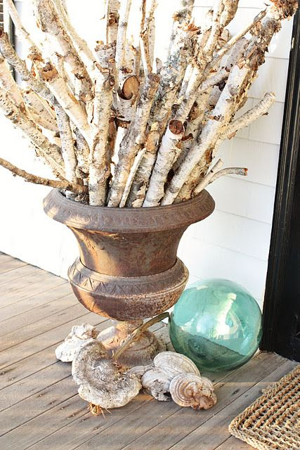a coastal fall decoration of a large urn, lots of birch branches and seashells and a float next to it
