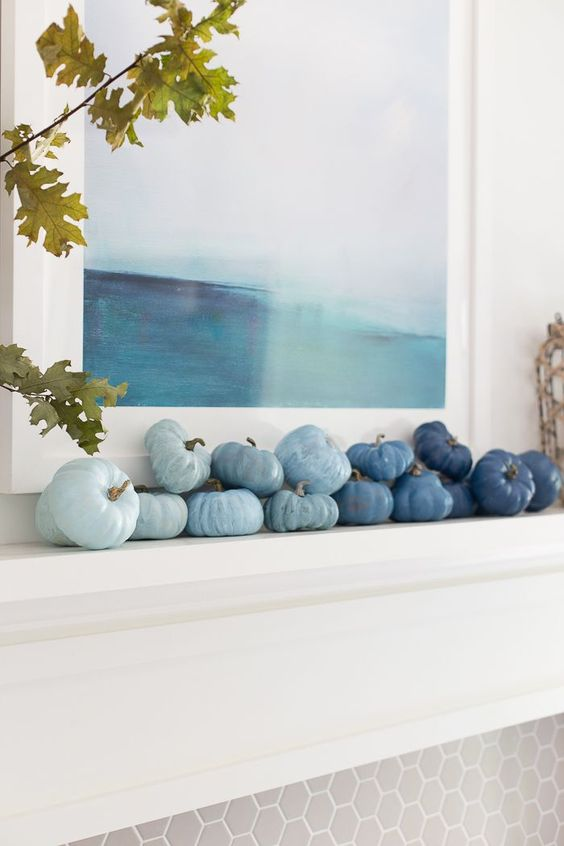a coastal fall mantel decorated with faux veggies in various shades of blue to create an ombre effect