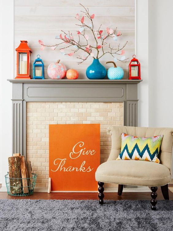 a cool colorful mantel with orange and blue candle lanterns, colorful pumpkins and branches with paper leaves