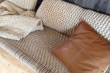 a cool woven bench with knit pillows and a matching blanket is a gorgeous place to have a nap