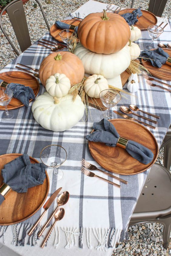 a cozy rustic fall tablescape with large pumpkins stacked, wheat, slate grey napkins and a plaid tablecloth, copper cutlery and wooden chargers