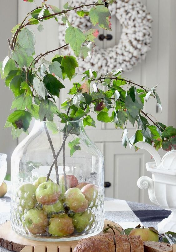 a creative fall centerpiece of a large jar with apples and some greenery branches