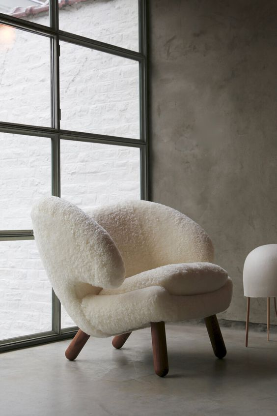a cute white faux fur chair with a fresh and modern take ona wingback and wooden legs is very welcoming