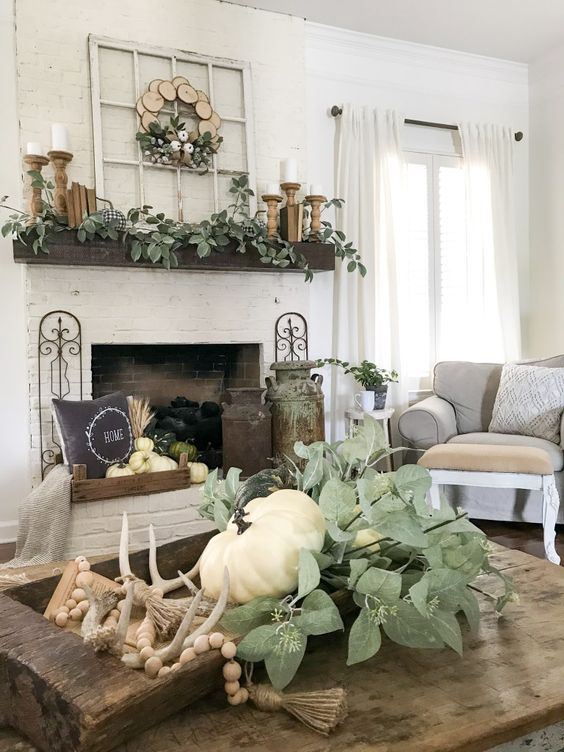 a dough bowl with a rosary, antlers, greenery and a white pumpkin for farmhouse coffee table decor