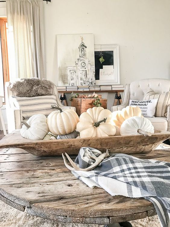 a dough bowl with natural and fabric pumpkins in neutrals, a plaid napkin and antlers