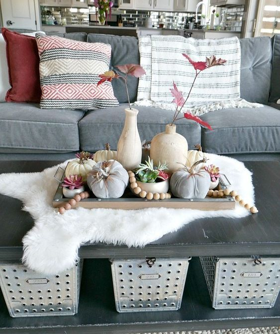 a fall coffee table styled with a wooden tray with wooden beads, natural and fabric pumpkins and red fall leaves in vases