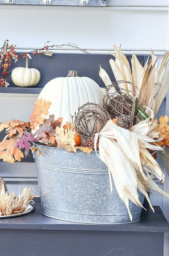 a fall decoration of a metal bucket with corn husks, leaves, pumpkins and vine balls