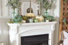 a fall mantel decorated with pinecones, faux pumpkins, pale greenery in tall bottles