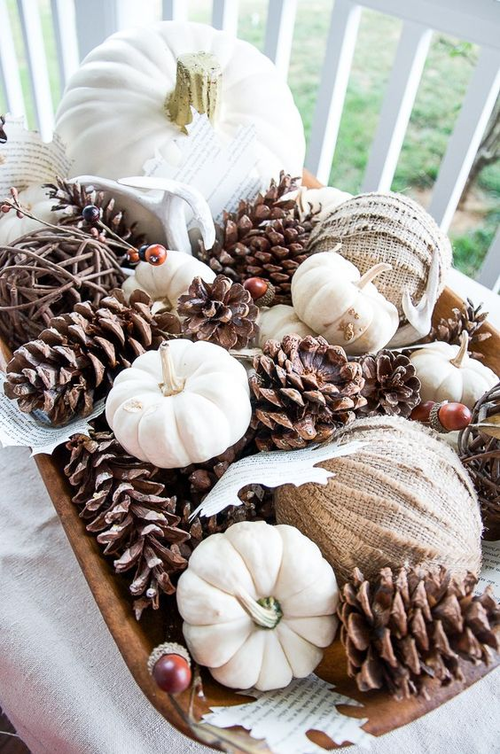 a fall party centerpiece with pinecones, natural white pumpkins, burlap balls and paper leaves