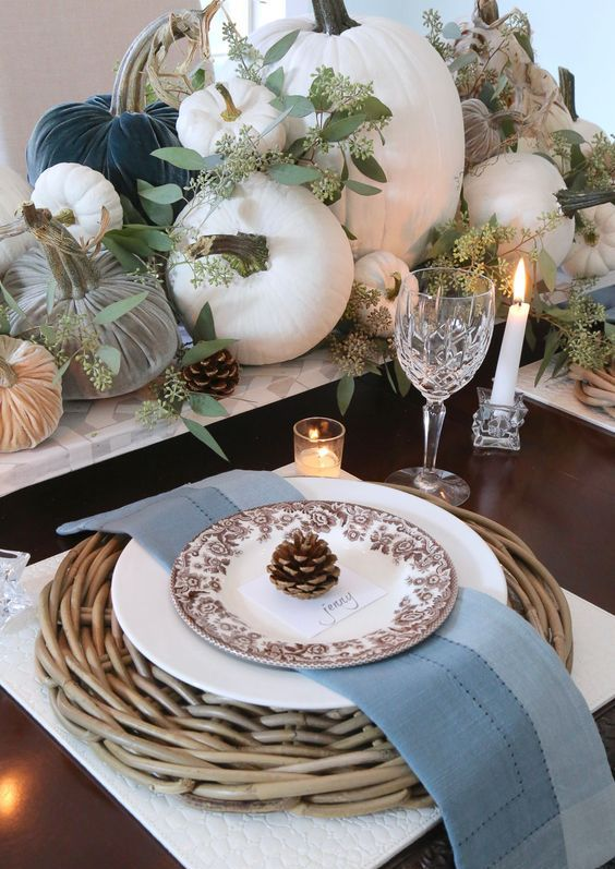 a fall table setting with woven placemats, pinecones, fabric and natural pumpkins and fresh eucalyptus