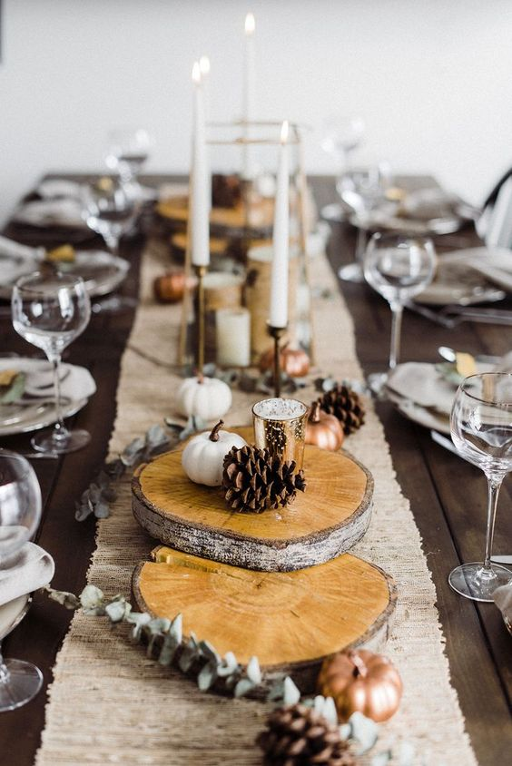 a fall tablescape with wood slices, pinecones, little faux pumpkins, a burlap runner for a natural feel