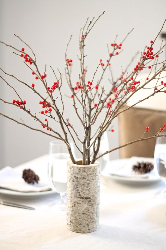 a large branch-imitating vase with branches and berries is a simple contemproary centerpiece for the fall