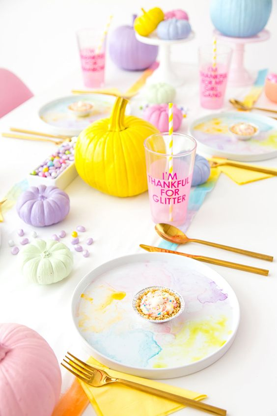 a lovely and bright pastel fall tablescape with pastel pumpkins, candies, marbled dishes and bold table runners