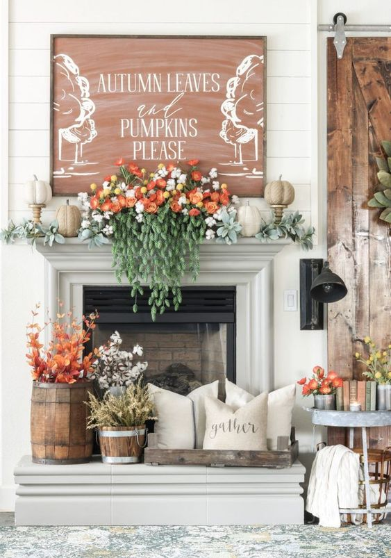 a lush fall mantel with pale greenery, faux pumpkins, gorgeous florals and cascading greenery, fall leaves and cotton in buckets and a fall sign
