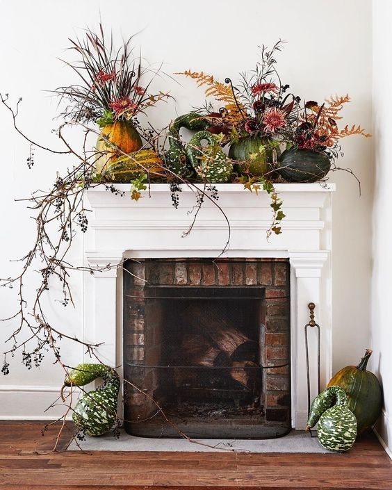 a lush harvest mantel decorated with greenery, long branches and pumpkins and gourds on the mantel