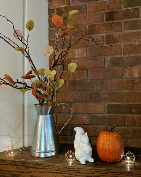 a metal jug with branches and fake fall leaves plus a pumpkin are simple fall decorations to go for