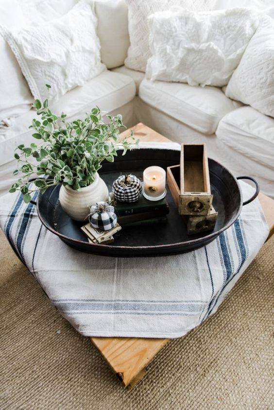 a metal tray with a candle, potted greenery, plaid pumpkins and wooden drawers for a famrhouse feel