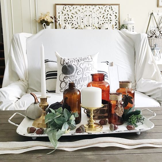 a metal tray with greenery, acorns, apothecary bottles, white candles and fabric pumpkins is a whimsy and cool decoration