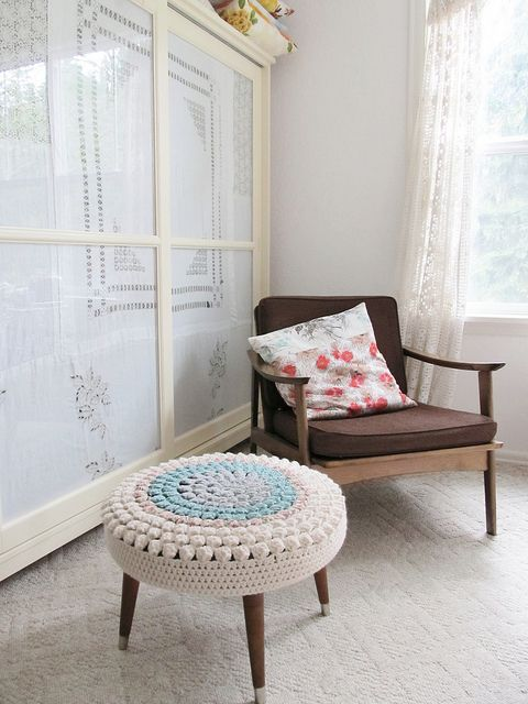 a mid-century modenr ottoman with a pastel crochet cover is a nice idea to add a soft touch of color and coziness
