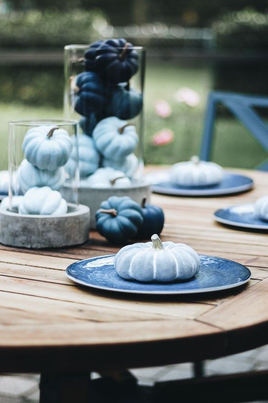 a modern blue fall table setting with light blue and navy pumpkins and plates is lovely