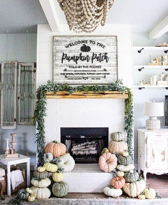 a modern farmhouse mantel with stacks of heirloom pumpkins, a greenery wreath and a large rustic sign