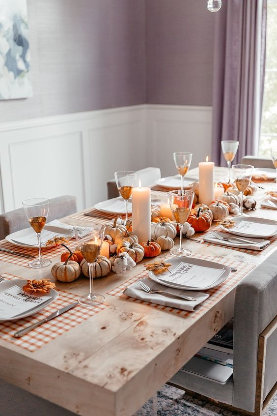a natural fall table setting with little faux pumpkins, pillar candles and plaid placemats