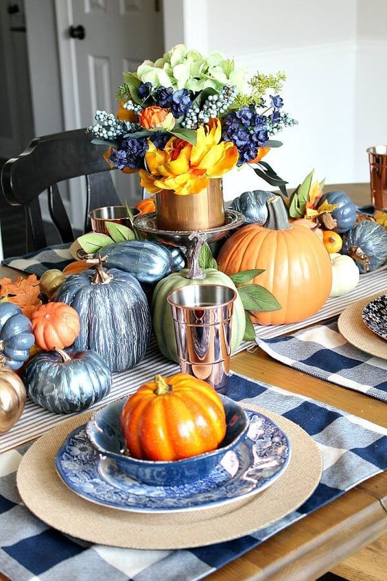 a navy and copper fall tablescape with painted pumpkins, a plaid placemat, a lush floral centerpiece
