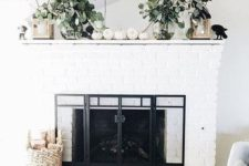 a neutral fal mantel with fresh greenery, white pumpkins, candle lanterns and a basket with branches