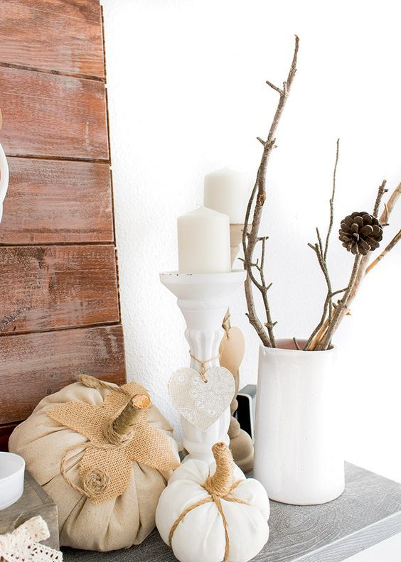 a neutral vintage inspired mantel with branches in a white vase and some faux white pumpkins and candles