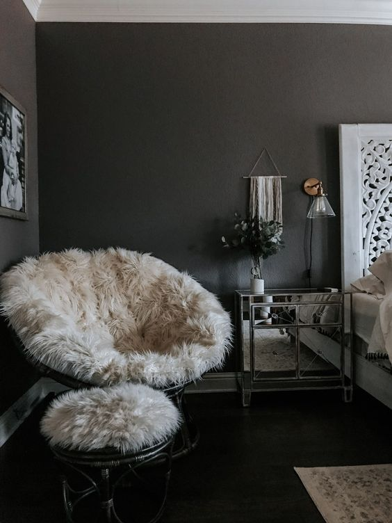 a papasan chair finished off with a white faux fur cover and a matching stool with such a cover for cold months