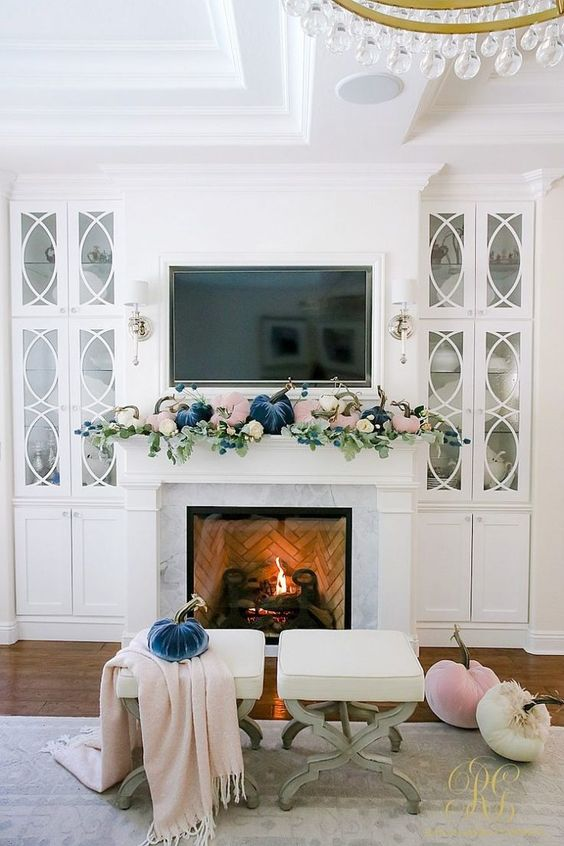 a pastel fall mantel with blush and navy velvet pumpkins and fresh greenery is a cool modern idea