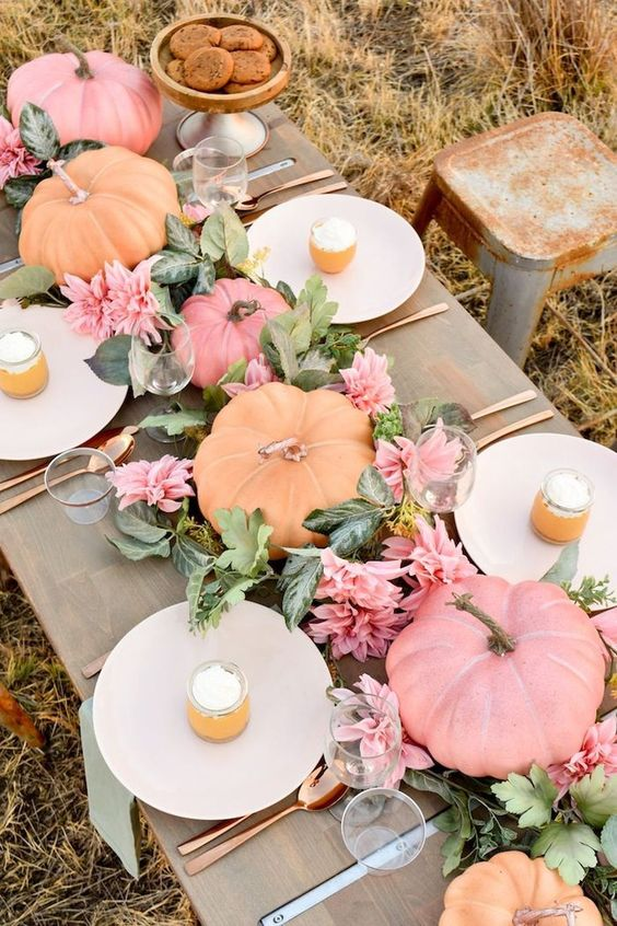 a pastel fall tablescape with pink blooms, greenery, pastel pumpkins and copper cutlery to finish off the look