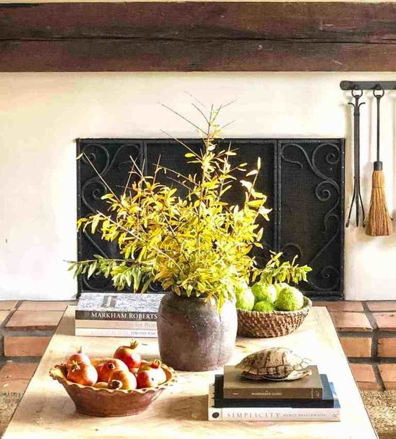 a pot with greenery branches, a wooden bowl with moss balls and a wooden bowl with pomegranates for natural decor