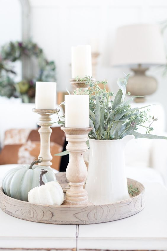 a round tray with green and white pumpkins, white candles in wooden candleholders and greenery in a white jug