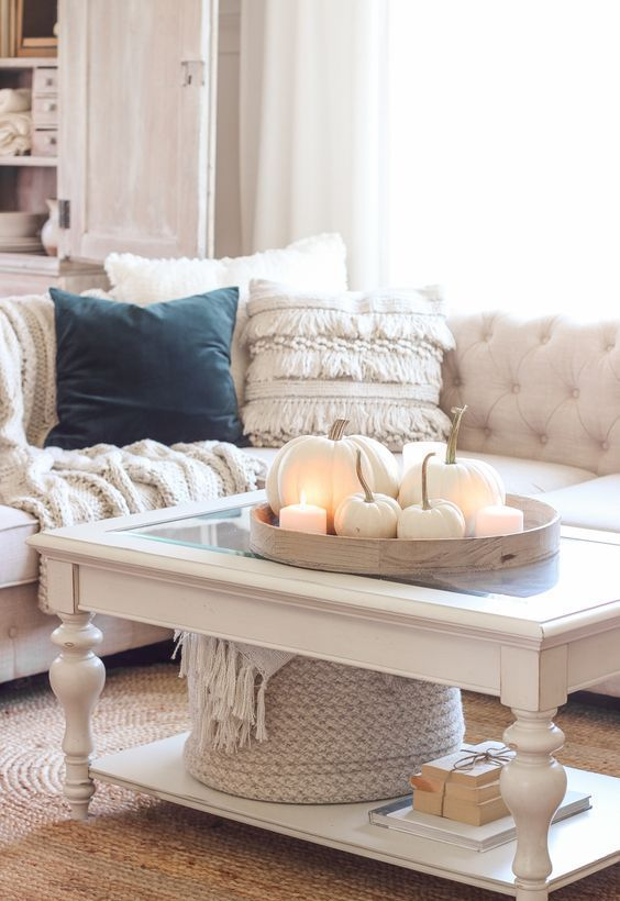 a round wooden tray with white pumpkins and candles is a simple yet very cute fall decoration in neutrals