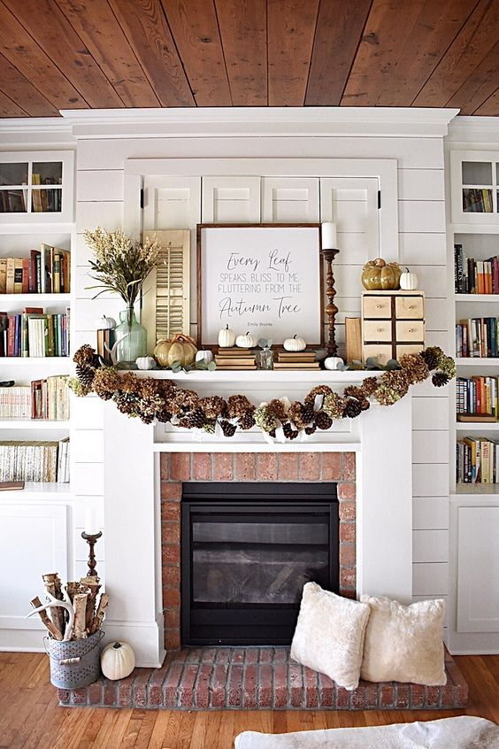 a rustic fall mantel with a pinecone and hydrangea garland, white pumpkins and faux porcelain ones, a branch arrangement in a bucket