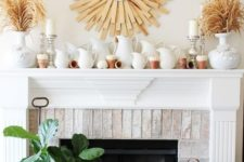 a rustic fall mantel with a sunurst decoration, dried herbs in vases, lots of jugs and tiny white pumpkins