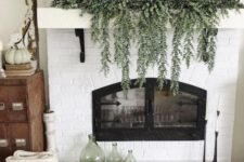 a rustic fall mantel with cascading greenery, white pumpkins with a wooden dough bowl plus green bottles