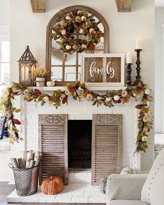 a rustic fall mantel with dried fall leaves and pumpkins, candles in wooden candle holders, wheat arrangements and a rustic sign