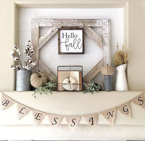 a rustic fall mantel with fabric pumpkins, wheat and cotton, a vintage book, a burlap banner and some greenery