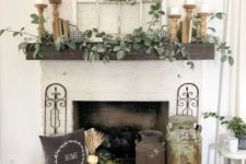 a rustic fall mantel with greenery, candles in wooden candleholders, a crate with white pumpkins, a pillow and a wood slice wreath