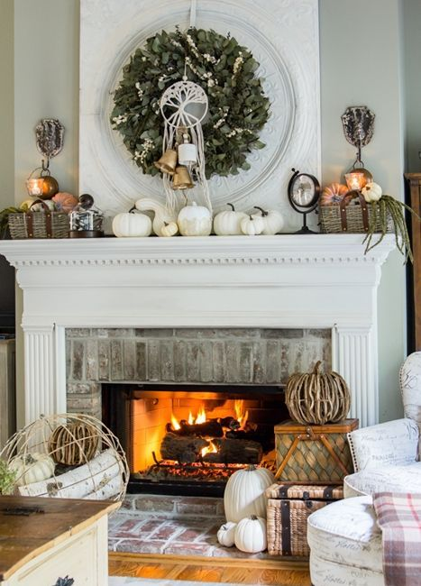 a rustic fall mantel with white pumpkins, baskets with faux pumpkins, a greenery wreath with bells and vine pumpkins