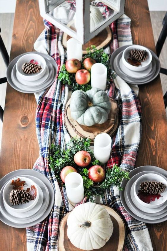 a rustic fall table setting with a plaid runner, pillar candles, heirloom pumpkins, apples, greenery and pinecones