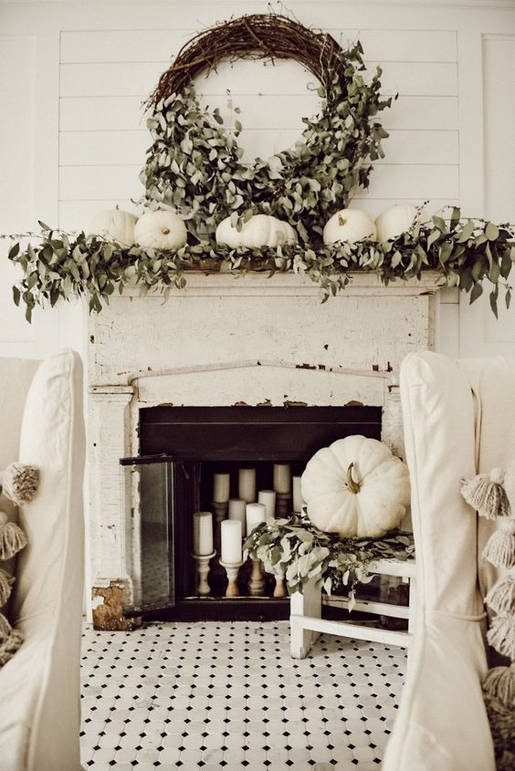 a shabby chic and rustic fall mantel with greenery, white pumpkins, a lush wreath with greenery and candles in the fireplace