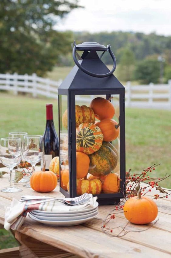 a simple and chic fall decoration of a black lantern filled with gourds and pumpkins