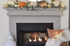 a simple contemporary fall mantel done with greenery and pumpkins of muted colors plus lights all over it