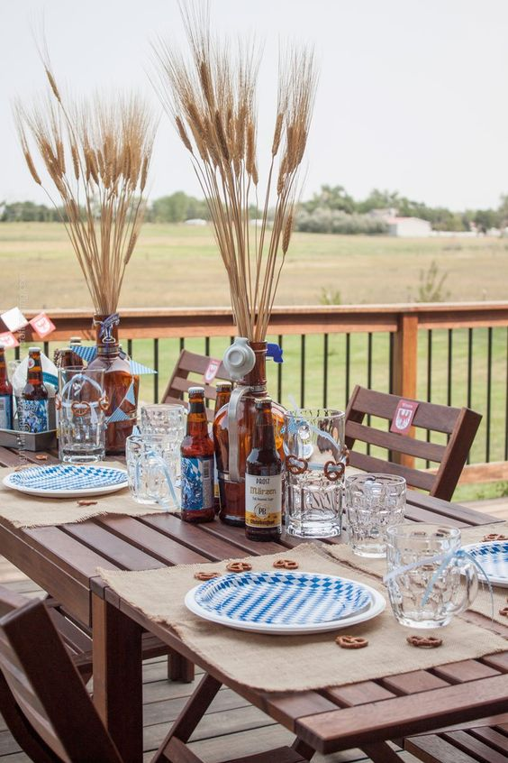 a simple outdoor fall tablescape done in beige and blue, with burlap placemats and wheat in bottles