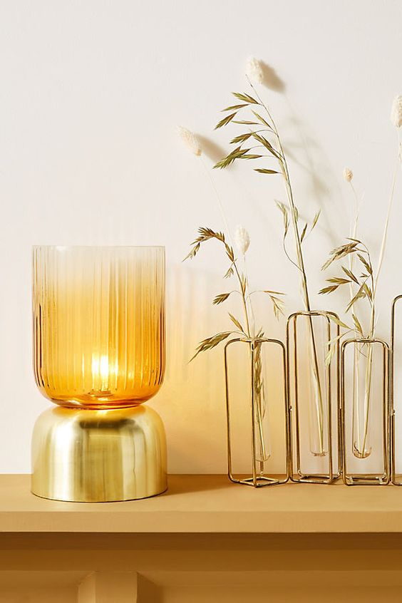 a stylish and elegant gold and tinted glass mug-shaped table lamp is a chic option for a contemporary space